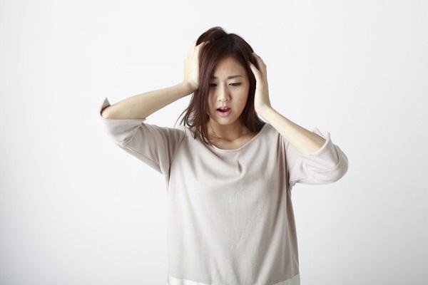 女性が頭を抱える
